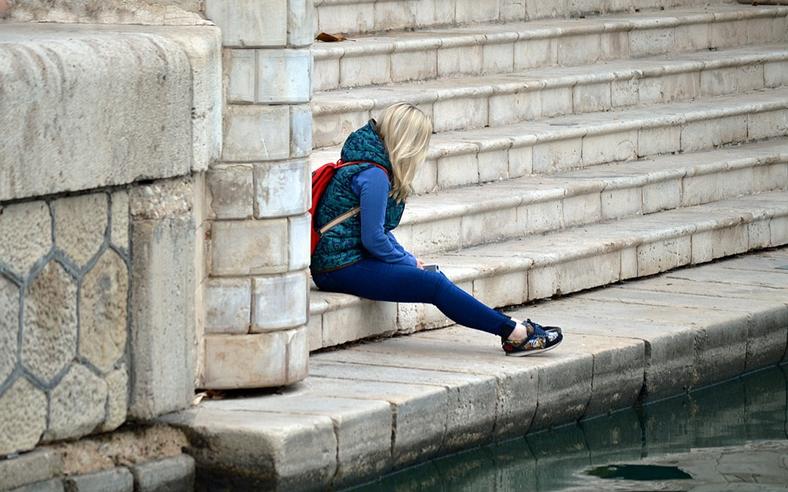 Frau auf Treppe, alleine, traurig